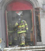 Portsmouth firefighter Russell Osgood walks out of the smoke-filled interior of the United Methodist Church